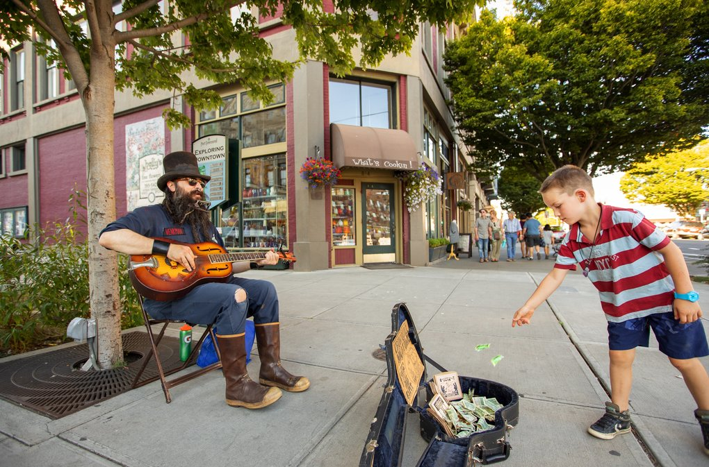 Busker Kit Stovepipe plays the guitar on Water Street in downtown Port Townsend. At right, Henry Norton, from Woodinville, tosses in a donation. (Mike Siegel / The Seattle Times)