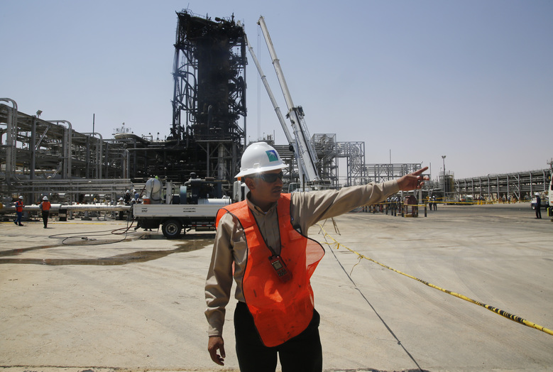 In this photo opportunity during a trip organized by Saudi information ministry, a worker points in front of the Khurais oil field in Khurais, Saudi Arabia, Friday, Sept. 20, 2019, after it was hit during Sept. 14 attack. Saudi officials brought journalists Friday to see the damage done in an attack the U.S. alleges Iran carried out. Iran denies that. Yemen's Houthi rebels claimed the assault. (AP Photo/Amr Nabil)
