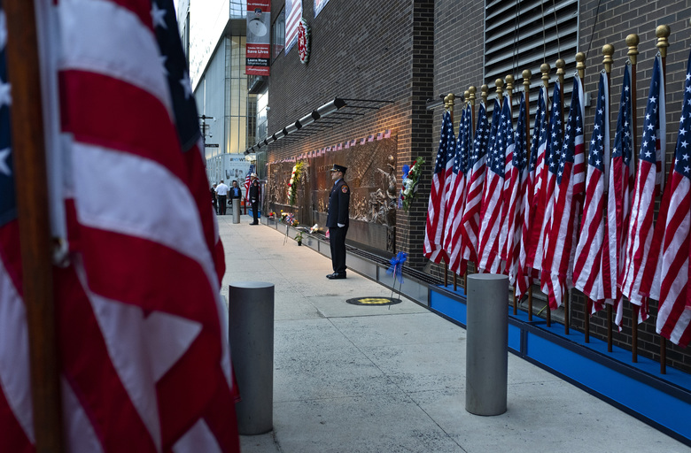 New York City firefighters stand at attention in front of a memorial on the side of a firehouse adjacent to One World Trade Center and the 9/11 Memorial site during ceremonies commemorating the 18th anniversary of the 9/11 terrorist attacks in New York on Wednesday, Sept. 11, 2019. (AP Photo/Craig Ruttle)