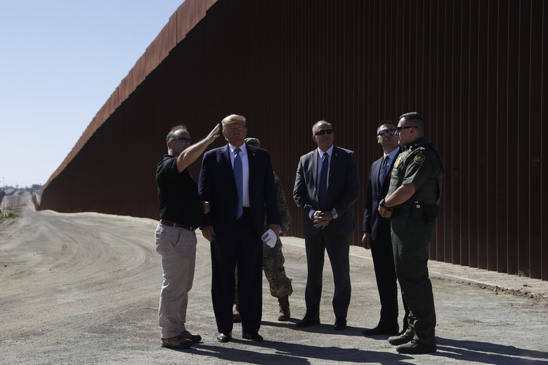 President Donald Trump tours a section of the southern border wall, Wednesday, Sept. 18, 2019, in Otay Mesa, Calif., with acting commissioner of Customs and Border Protection Mark Morgan, third from right, and acting Homeland Secretary Kevin McAleenan, second from right.  (AP Photo/Evan Vucci)