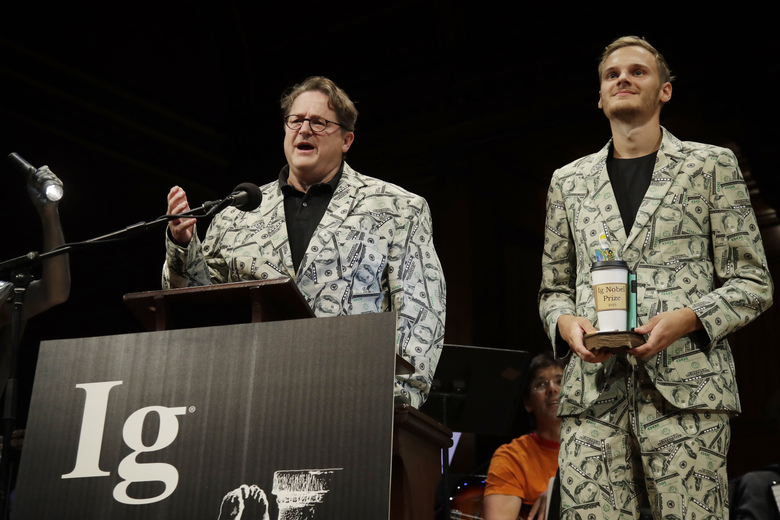 Andreas Voss, left, and his son Timothy Voss, of The Netherlands, receive the Ig Nobel award in economics for testing which country's paper money is best at transmitting dangerous bacteria, at the 29th annual Ig Nobel awards ceremony at Harvard University, Thursday, Sept. 12, 2019, in Cambridge, Mass. The spoof prizes for weird and sometimes head-scratching scientific achievement are bestowed by the Annals of Improbable Research magazine, and handed out by real Nobel laureates. (AP Photo/Elise Amendola)