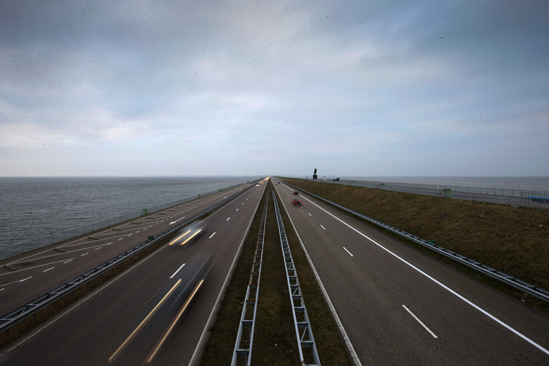 In this photo taken Sunday March 8, 2015, traffic moves over the Afsluitdijk, a dike and causeway, separating Wadden Sea, right, from western europe's largest lake, IJsselmeer lake, left, between Den Oever and Wieringen, northern Netherlands. Rising in a thin line through the surface of waters separating the provinces of North Holland and Friesland, the 87-year-old Afsluitdijk is one of the low-lying Netherlands' key defenses against the sea. With climate change bringing more powerful storms and rising sea levels, it's getting a major makeover. (AP Photo/Peter Dejong)