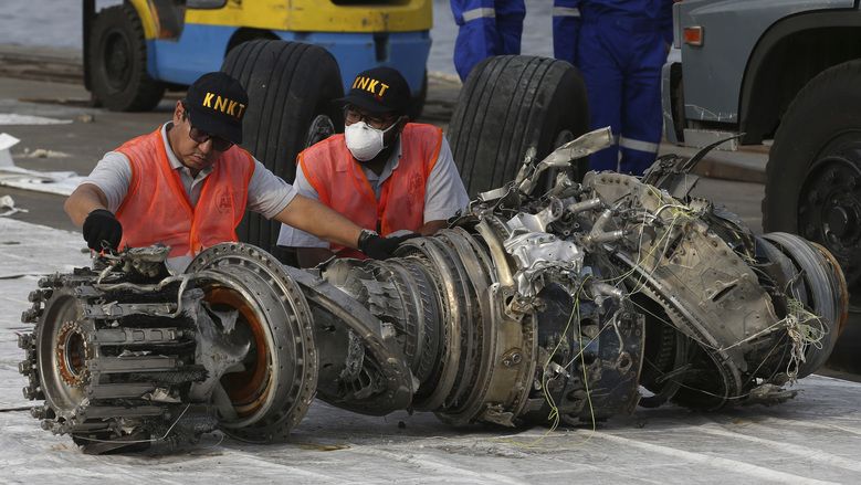 FILE – In this Nov. 4, 2018, file photo officials inspect an engine recovered the crashed Lion Air jet in Jakarta, Indonesia.  Chicago law firm says it has settled lawsuits against Boeing on behalf of the families of 11 passengers killed in the crash of a Lion Air jet off the coast of Indonesia. (AP Photo/Achmad Ibrahim, File)