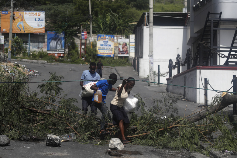 Residents walk through a barricade set up by protesters in Port-au-Prince, Haiti, Monday, Sept. 30, 2019. Opposition leaders are calling for a nationwide push Monday to block streets and paralyze Haiti's economy as they press for Moise to give up power, and tens of thousands of their young supporters were expected to heed the call. (AP Photo/Rebecca Blackwell)