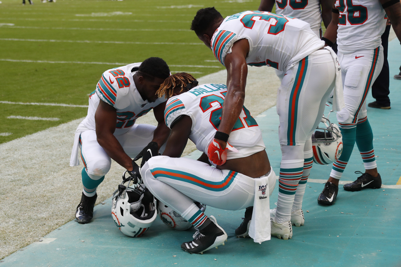 Miami Dolphins running backs Mark Walton (22) and Kenyan Drake (32), console running back Kalen Ballage (27), during the second half at an NFL football game against the New England Patriots, Sunday, Sept. 15, 2019, in Miami Gardens, Fla. The Patriots defeated the Dolphins 43-0. (AP Photo/Wilfredo Lee)