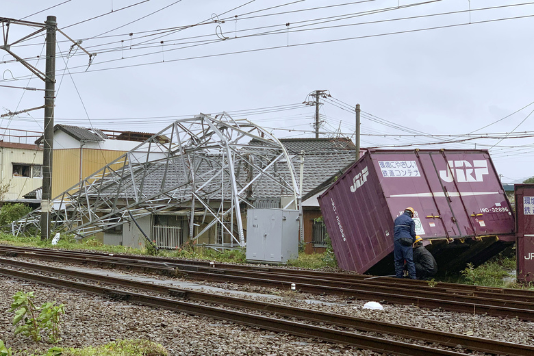 A cargo container and a steel tower are damaged by winds after Typhoon Tapah hit Nobeoka, Miyazaki prefecture, southwestern Japan Sunday, Sept. 22, 2019. The powerful typhoon is heading northeast to Japan's main island of Honshu after lashing parts of the country's southern islands with heavy rains and winds that caused flooding and some minor injuries. (Kyodo News via AP)