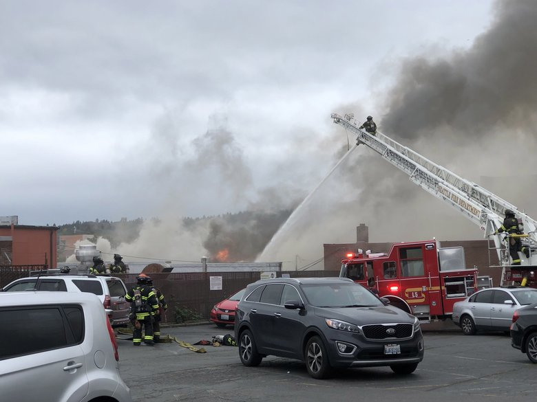 People were advised to avoid Northwest Market Street in Ballard as crews attempt to put out a large fire in a commercial building. (Amanda Snyder / The Seattle Times)