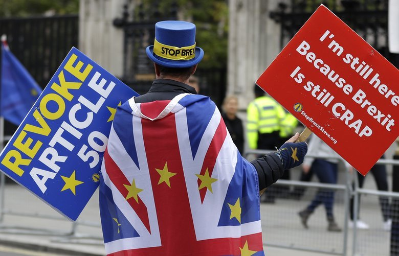 Anti-Brexit campaigner Steve Bray walks near Parliament in London, Tuesday, Oct. 8, 2019. The British government said Tuesday that the chances of a Brexit deal with the European Union were fading fast, as the two sides remained unwilling to shift from their entrenched positions. (AP Photo/Kirsty Wigglesworth) LKW106 LKW106