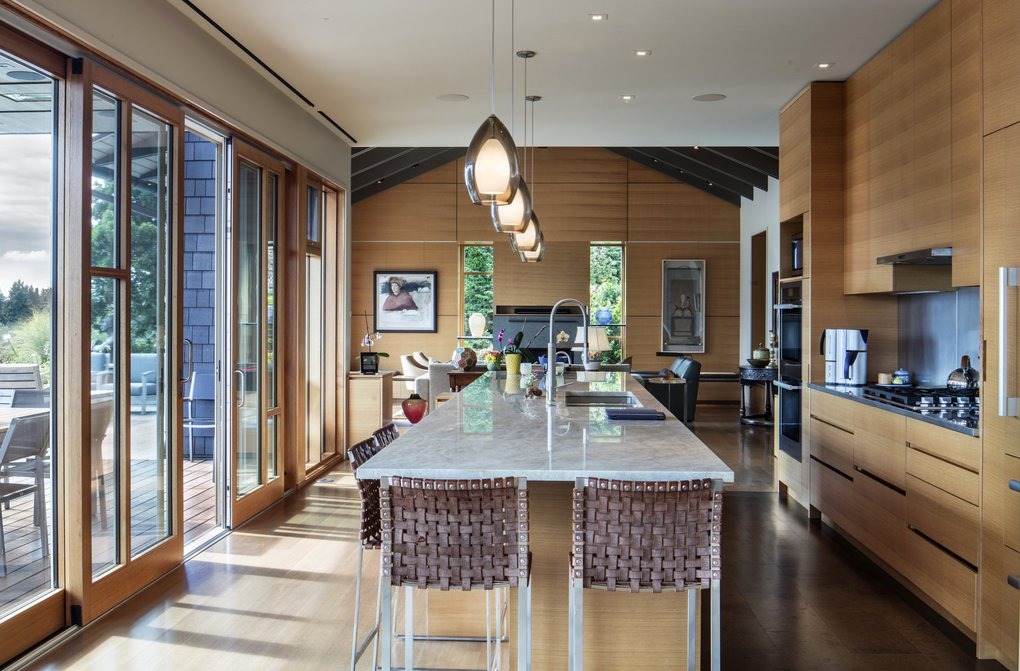 """""""On the main level, a connected kitchen, living  and dining space opens onto an ipe deck and a stone terrace that steps down to a hillside garden,"""" says architect Geoff Prentiss. """"From the house, the deck or the terrace, you feel as though you're floating above the lake."""" (Steve Ringman / The Seattle Times)"""