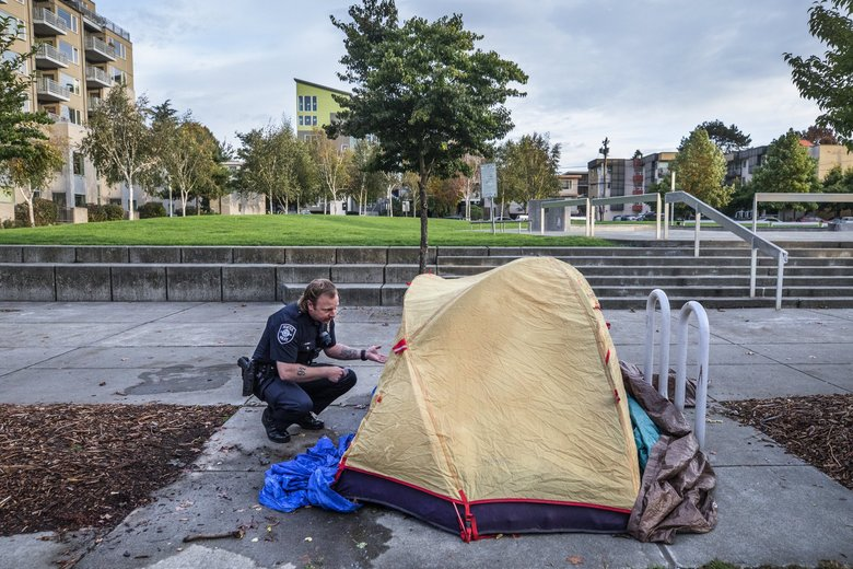 Community police officer Nic Boys reminds a homeless couple that they need to move their tent off the sidewalk near the Ballard Commons Park.    (Steve Ringman / The Seattle Times)