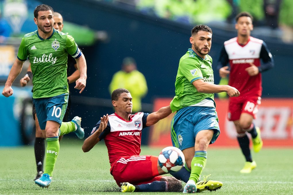 FC Dallas defender Reggie Cannon (2) slides into Seattle Sounders midfielder Cristian Roldan (7) during the first half of the MLS playoffs between the Seattle Sounders and FC Dallas at CenturyLink Field in Seattle, WA, on Oct. 19, 2019. Cannon received a yellow card for the move. (Andy Bao / The Seattle Times)