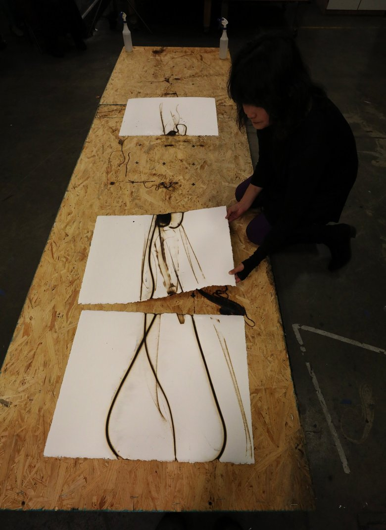 Etsuko Ichikawa gathers the panels of a triptych just produced before an audience at Pratt Fine Arts Center. (Alan Berner / The Seattle Times)