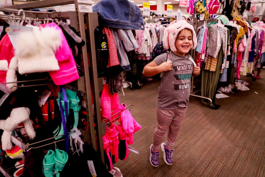 First grader Clara Holmes hops while trying on new hats and clothes at Northgate Target in Seattle last week. The Assistance League of Seattle's  Operation School Bell program works with referrals from Seattle Public Schools to provide new clothing for around 2,600 K-8 students during 13 events in October at Target in Westwood Village, Westfield Southcenter's JCPenney and the Northgate Target. For more information: https://www.assistanceleague.org/seattle/ (Erika Schultz / The Seattle Times)