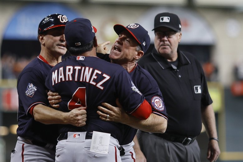 Washington Nationals manager Dave Martinez has to be restrained after being ejected for arguing an interference call during the seventh inning of Game 6 of the baseball World Series against the Houston Astros Tuesday, Oct. 29, 2019, in Houston.  (Matt Slocum / The Associated Press)