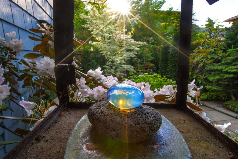 Clouds are reflected as the setting sun illuminates an oval piece of opalescent glass, housed in an 18th-century Japanese shrine house near the back door of Curtis Steiner's home. (Mike Siegel / The Seattle Times)