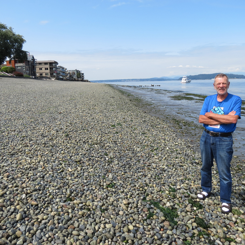 NOW: Phil Hoffman stands just east of the site of the former Alki-Manchester ferry dock, whose pilings peek out of the low-tide surf behind him to his right. You can see Hoffman's prolific research articles on all topics Alki, including the Alki-to-Manchester ferry, at <em>alkihistoryproject.com.</em> (Clay Eals)