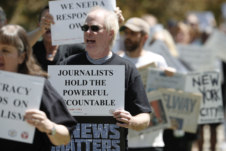 Denver Post employees walk outside the newspaper's office and printing plant during a rally against the paper's venture-capital ownership group, Alden Global Capital, in May 2018. (AP Photo / David Zalubowski)