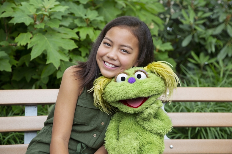 """Salia Woodbury, 10, whose parents are in recovery, with """"Sesame Street"""" character Karli, who is in foster care. (Flynn Larsen / Sesame Workshop via AP)"""