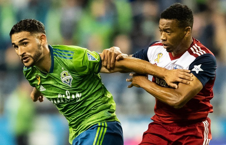Seattle Sounders midfielder Cristian Roldan (7) attempts to fend off Dallas FC's Jacori Hayes (15) during the MLS soccer game between the Seattle Sounders and Dallas FC on Sept. 18, 2019. 211519