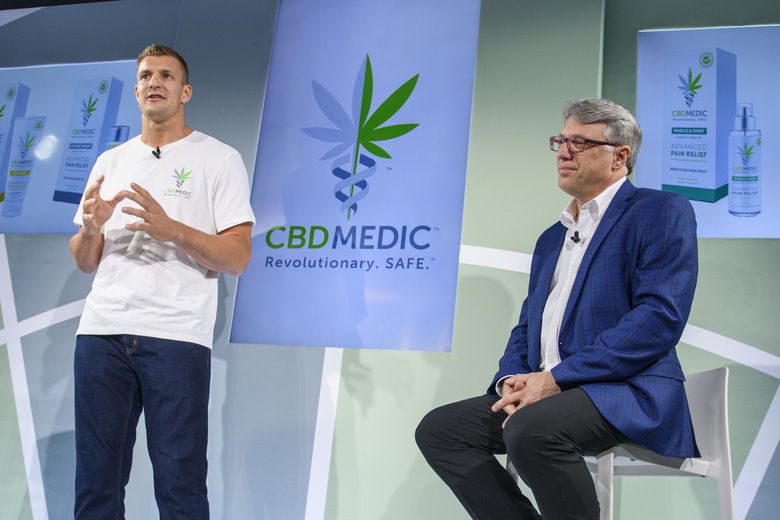 FILE – In this Aug. 27, 2019, file photo, former New England Patriots tight end Rob Gronkowski, left, speaks as Perry Antelman, CEO of Abacus Health Products, listens during a news conference announcing in New York.  The home of the New England Patriots has a new sponsorship deal with Abacus Health Products that will put the cannabidiol company's hemp leaf logo on a water tower looming over the stadium and on a sign overlooking an entrance.  (AP Photo/Corey Sipkin, File)