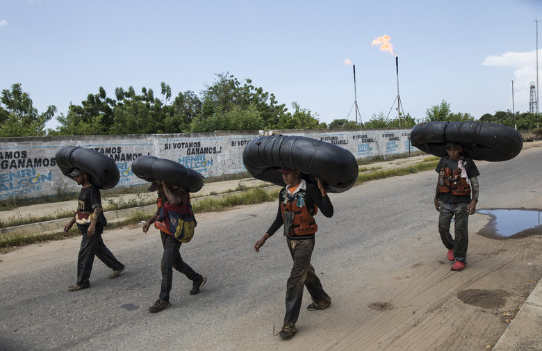 Oil-covered fishermen carry home the truck tire inner tubes they use to float on in Lake Maracaibo in Cabimas, Venezuela, July 12, 2019. Venezuelan fishermen are the ones more at risk from persistent long-term exposure to the oil in Lake Maracaibo, compared to the consumers occasionally exposed to the oil-soaked seafood, according to Cornelis Elferink, a professor of pharmacology and toxicology at the University of Texas Medical Branch at Galveston. (AP Photo/Rodrigo Abd)