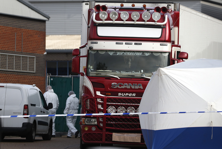 Police forensic officers attend the scene after a truck was found to contain a large number of dead bodies, in Thurrock, South England, early Wednesday Oct. 23, 2019. Police in southeastern England said that 39 people were found dead Wednesday inside a truck container believed to have come from Bulgaria. (AP Photo/Alastair Grant)