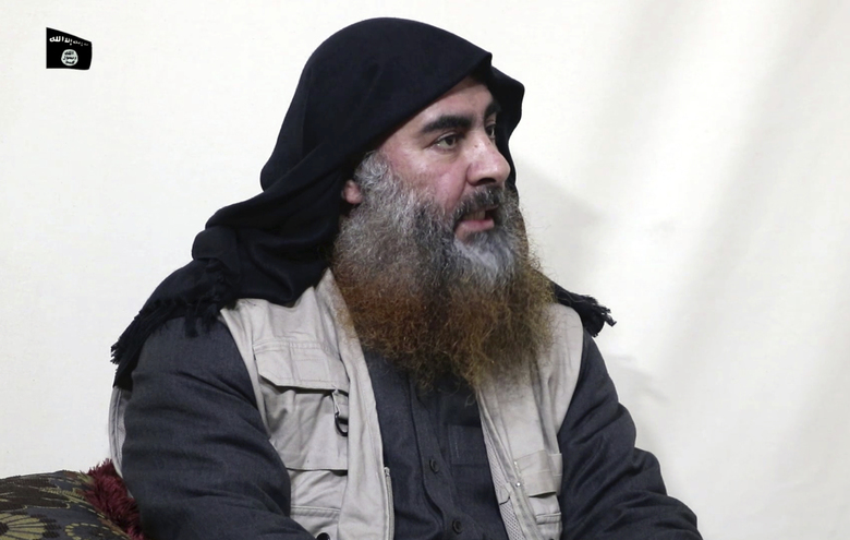 """FILE – This file image made from video posted on a militant website April 29, 2019, purports to show the leader of the Islamic State group, Abu Bakr al-Baghdadi, being interviewed by his group's Al-Furqan media outlet. The IS erupted from the chaos of Syria and Iraq's conflicts and swiftly did what no Islamic militant group had done before, conquering a giant stretch of territory and declaring itself a """"caliphate."""" U.S. officials said late Saturday, Oct. 26, 2019 that al-Baghdadi was the target of an American raid in Syria and may have died in an explosion. (Al-Furqan media via AP, File)"""