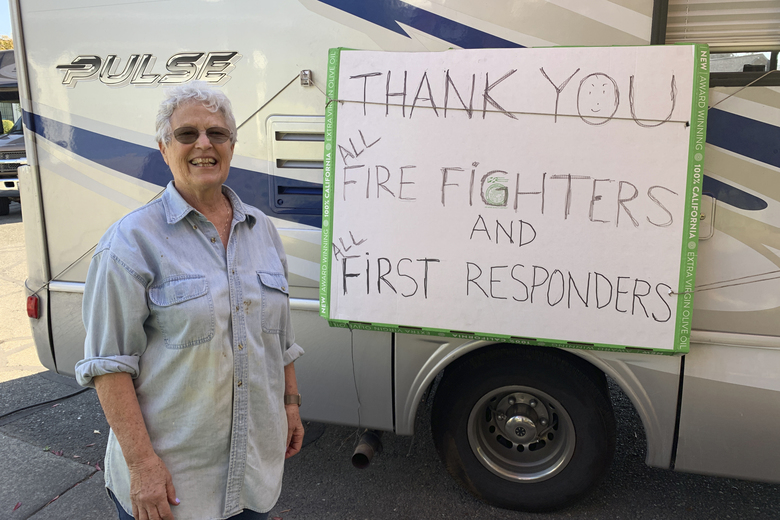 """Lynn Darst shows a sign she hung on her motor home where she and her husband stayed after they were evacuated from their house in Windsor, Calif., Thursday, Oct. 31, 2019. Darst and her husband were camped out in their motor home on the edge of their seats for four days wondering if their house would survive yet another wildfire menacing Sonoma County. Flames had come close to their neighborhood of spacious homes surrounding by vineyards two years ago and the danger was closing in again. """"We were comfortable, but fearful of what the consequences could be,"""" Darst said Thursday, the day after finding her home had been spared once again. (AP Photo/Terry Chea)"""