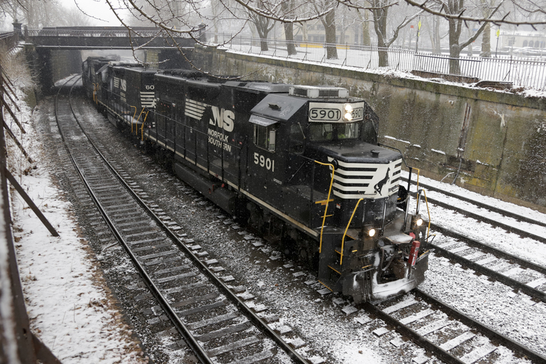 FILE – In this March 3, 2019, file photo a Norfolk Southern freight train passes through the Northside of Pittsburgh as show begins to fall. Norfolk Southern reports financial earns on Wednesday, Oct. 23. (AP Photo/Gene J. Puskar, File)