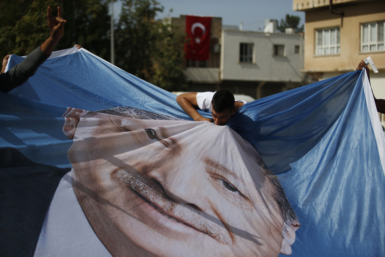A man kisses a poster of Turkey's President Recep Tayyip Erdogan during show of support by about a dozen people for Turkey's operation in Syria, in the border town of Akcakale, Sanliurfa province, southeastern Turkey, on Monday, Oct. 14, 2019. Erdogan has criticized NATO allies which are looking to broaden an arms embargo against Turkey over its push into northern Syria.  (AP Photo/Lefteris Pitarakis)