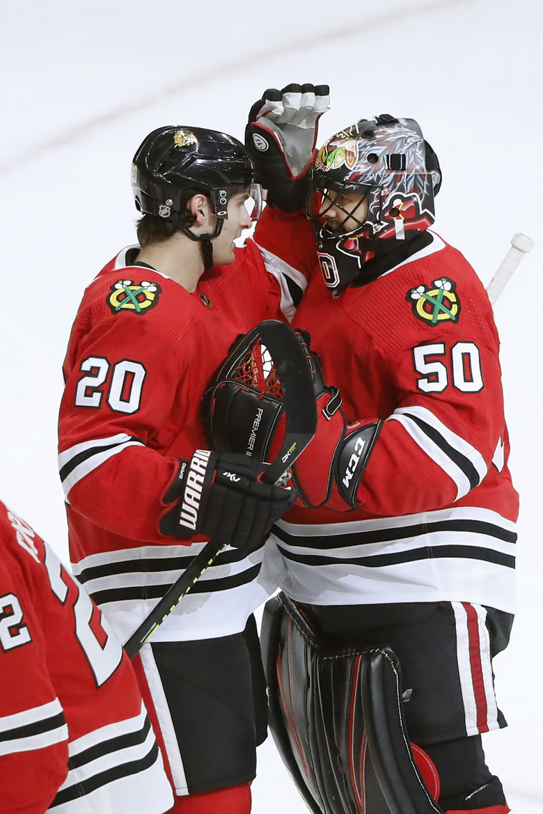 The Chicago Blackhawks' Brandon Saad (20) and goaltender Corey Crawford celebrate their win over the Edmonton Oilers in an NHL hockey game Monday, Oct. 14, 2019, in Chicago. (AP Photo/Charles Rex Arbogast)