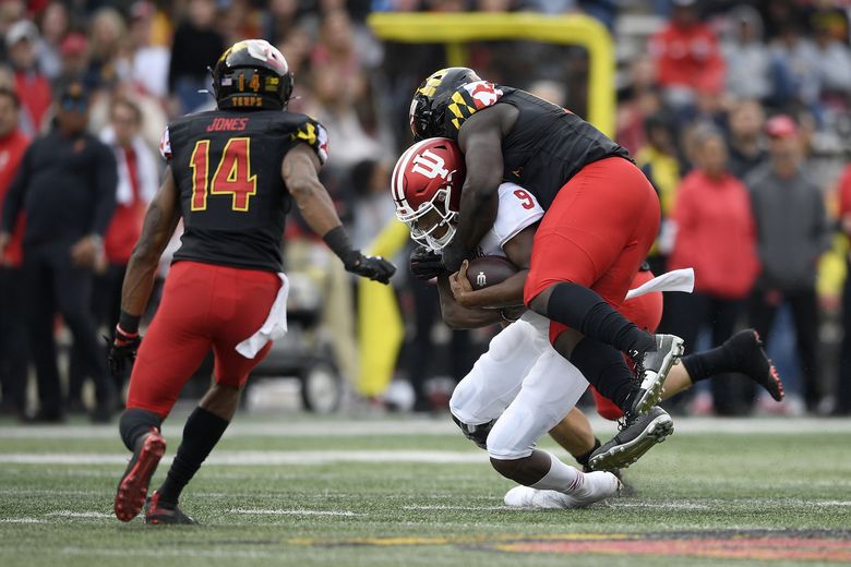 Maryland defensive lineman Oluwaseun Oluwatimi, right, tackles Indiana quarterback Michael Penix Jr. (9) during the first half of an NCAA college football game, Saturday, Oct. 19, 2019, in College Park, Md. Maryland defensive back Deon Jones (14) looks on. (AP Photo/Nick Wass)