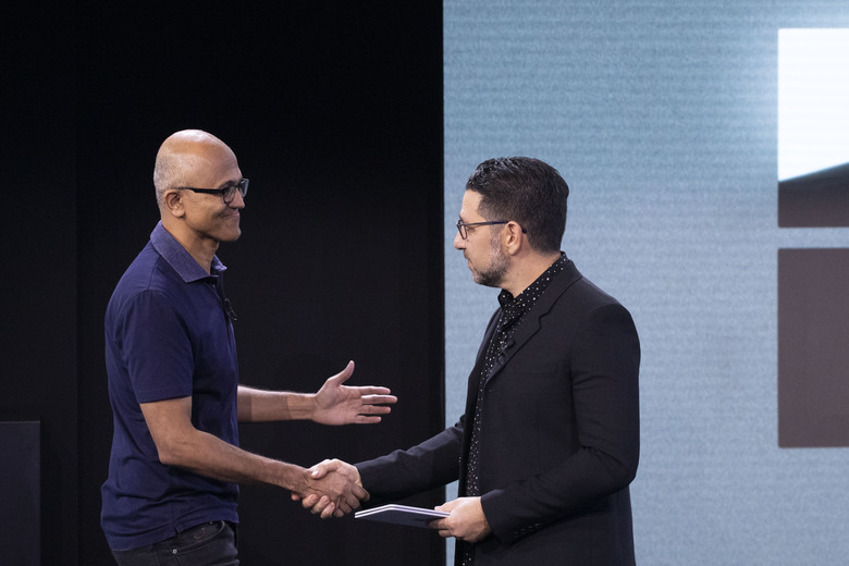 CORRECTS SPELLING OF FIRST NAME TO SATYA INSTEAD OF SAYS – Microsoft CEO Satya Nadella, left, shakes hands with Chief Product Officer Panos Panay, who is holding a Surface Duo at an event Wednesday, Oct. 2, 2019, in New York. (AP Photo/Mark Lennihan)