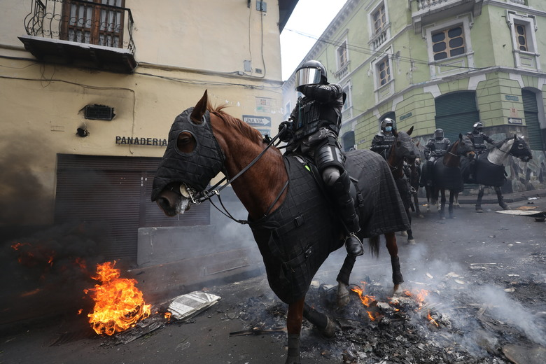 Mounted police cross a burning barricade in chase of anti-government demonstrators during a nationwide strike against President Lenin Moreno and his economic policies, in Quito, Ecuador, Wednesday, Oct. 9, 2019. Ecuador's military has warned people who plan to participate in a national strike over fuel price hikes to avoid acts of violence. The military says it will enforce the law during the planned strike Wednesday, following days of unrest that led Moreno to move government operations from Quito to the port of Guayaquil. (AP Photo/Fernando Vergara)