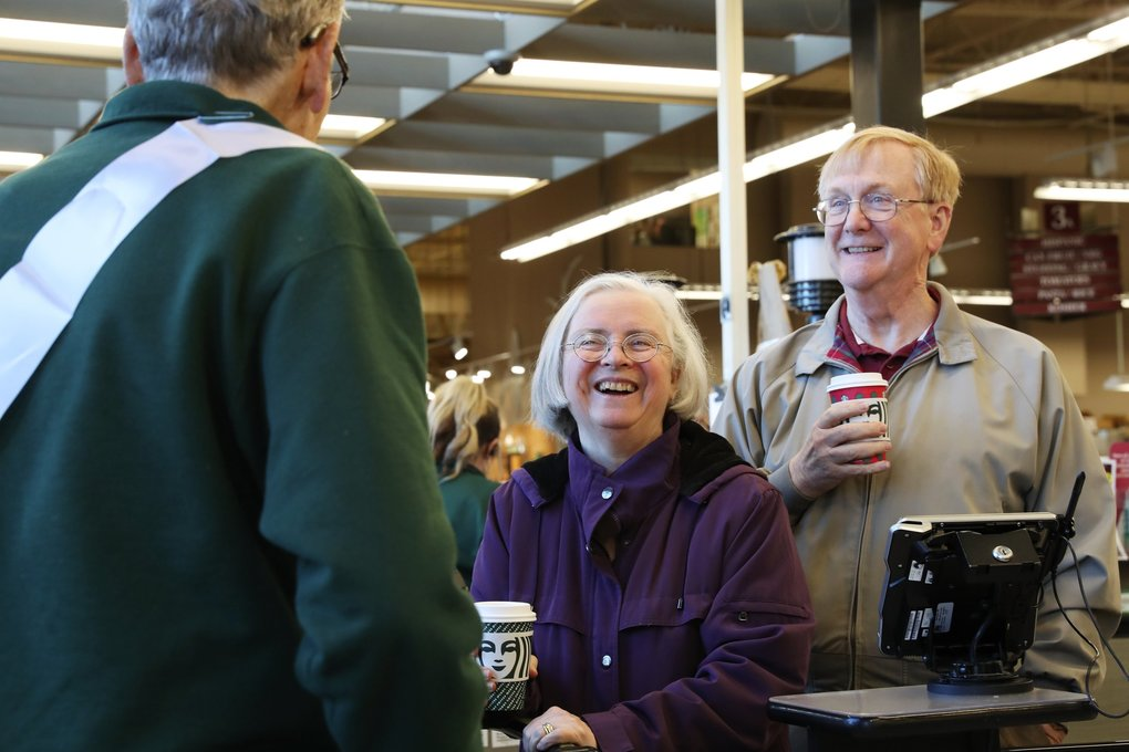 """Chuck Elvig visits with customers Susan and Steve Beatty after bagging their groceries. Elvig, who lives close by, told customers """"I'm retiring but I'm not leaving."""" (Ken Lambert / The Seattle Times)"""