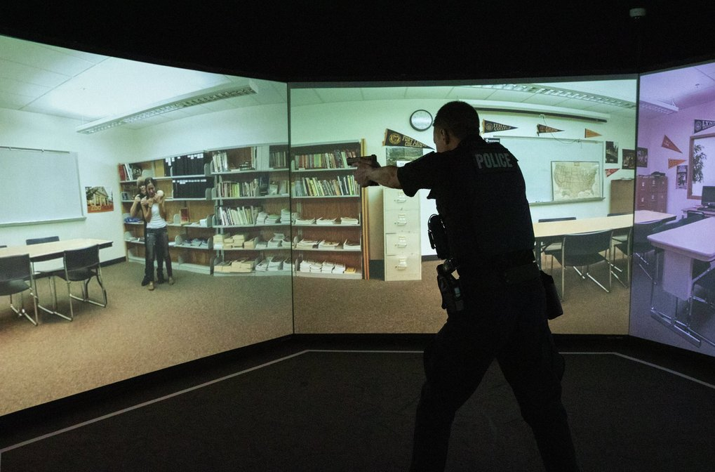 In a simulated hostage situation, Camas police Officer Kevin Hermann points his gun in a training apparatus at the Criminal Justice Training Center in Burien. After officers run through a scenario in the simulator, they discuss the outcome with training specialists and other officers. (Ellen M. Banner / The Seattle Times)