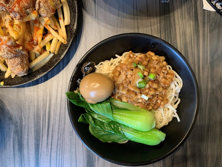 Dry noodles come with a pork ragu, baby bok choy and a soy-stained egg. (Lena Neufeld)