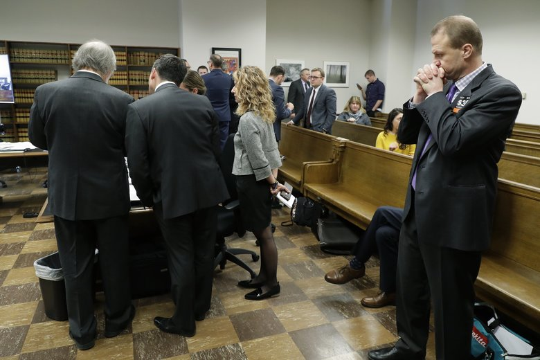 Tim Eyman, right, I-976  promoter, stands by as attorneys for the state of Washington confer during a break in a King County Superior Court hearing Tuesday. (Ted S. Warren / The Associated Press)