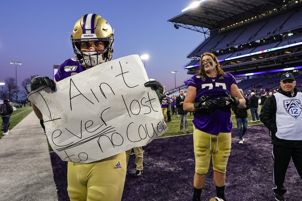 Jaren Hilbers grabs a sign with the sentiments share by his Husky teammates following their 31-13 win over WSU Friday. (Dean Rutz / The Seattle Times)