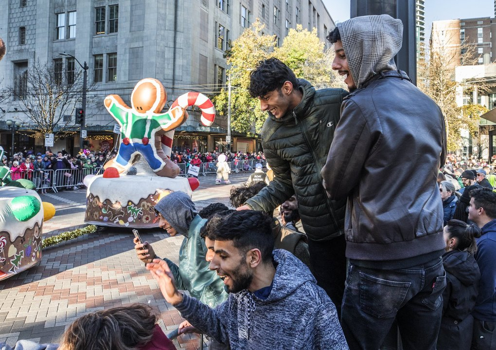Elevated parade watchers lean in as the inflatable Candy Cane Train passes Macy's during the holiday parade Friday morning in Seattle.    (Steve Ringman / The Seattle Times)