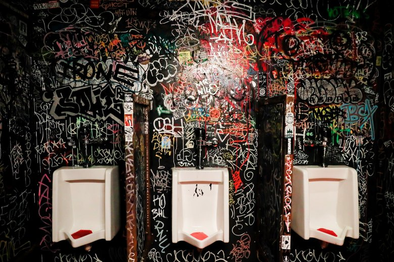 Floor-to-ceiling graffiti covers the bathroom walls at Jupiter Bar in Seattle. (Erika Schultz / The Seattle Times)
