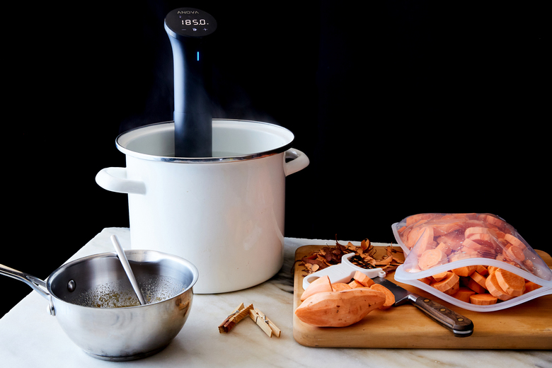 A sous-vide machine and sweet potatoes, in New York, Nov. 4, 2019. The kitchen tool can make preparing a Thanksgiving meal much easier, whether you're stressing over the turkey or looking for a way to cook and reheat potatoes. Food Stylist: Barrett Washburne. (Linda Xiao/The New York Times)