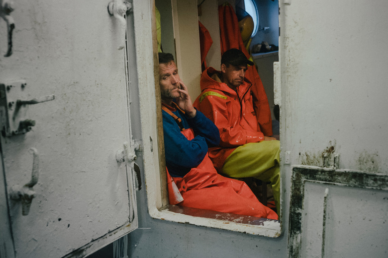 Night shift crewmen await the next haul aboard the Einar Hàlfdàns in waters off of the Westfjords region of Iceland. Warming waters associated with climate change are causing some fish to seek cooler waters elsewhere, beyond the reach of Icelandic fishermen. (Nanna Heitmann/The New York Times)