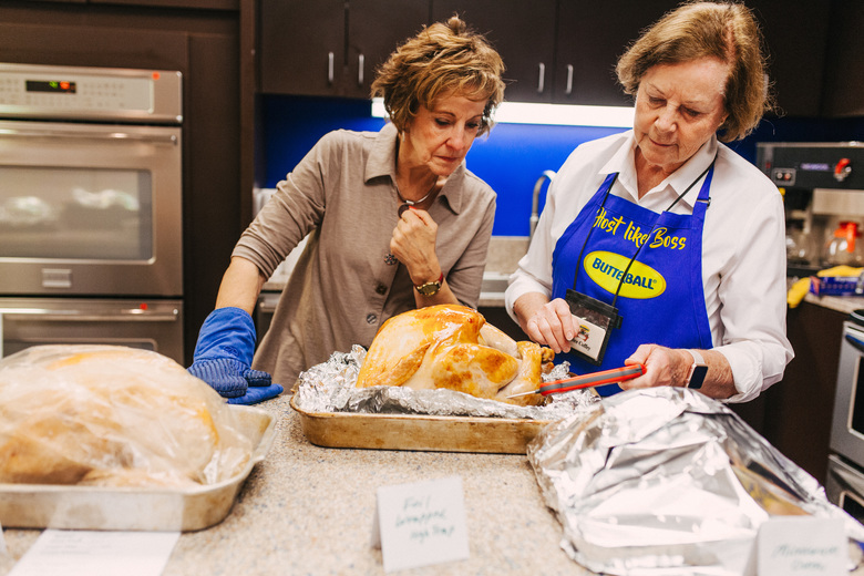 Phyllis Kramer, left, and Alice Coffrey, who have been working the Butterball Turkey Talk-Line for a collective 42 years, check the temperature of a turkey in the company's test kitchen in Naperville, Ill., Oct. 15, 2019. As Thanksgiving looms, no algorithm can comfort hordes of harried cooks like the 38-year-old Turkey Talk-Line. (Danielle Scruggs / The New York Times)