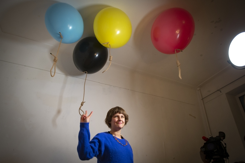 In this photo taken on Sunday, Oct. 27, 2019, Austrian artist Michele Pagel poses for a photo in front of her work showing rope nooses suspended from balloons bringing an issue often dismissed to the periphery of Russian society back to its center of attention at an opening ceremony of her exhibition in Moscow, Russia, Pagel 's show 'Polly wants a Cracker', focuses on domestic abuse. Moscow's suburbs are the focus of a major international art exhibition that has just opened in the Russian capital. The exhibit uses contemporary art to explore the many hidden facets of life beyond the Russian capital's nucleus. Austrian cultural attache says the 'real' Moscow where most of the city's 12.6 million people live, is outside the center. (AP Photo/Alexander Zemlianichenko)