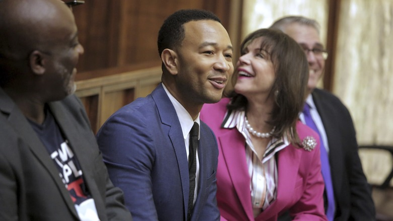 Singer songwriter John Legend, second from left, joins, from left, Desmond Meade, president of the Florida Rights Restoration Coalition, State Attorney Katherine Fernandez Rundle and Public defender, Carlos Martinez, during a special court hearing aimed at restoring voting rights to former felons under Florida's Amendment 4, Friday, Nov. 8, 2019, in Miami. (Jose A. Iglesias/Miami Herald via AP)