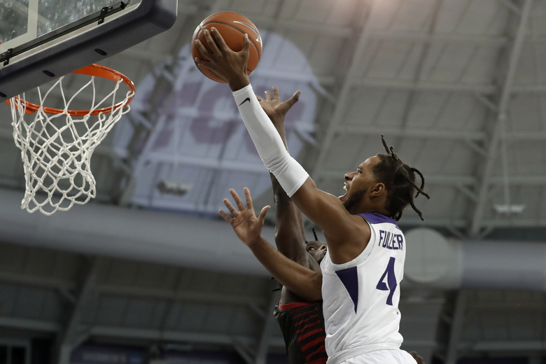 TCU guard PJ Fuller (4) shoots next to Louisiana-Lafayette's Dou Gueye during the second half of an NCAA college basketball game in Fort Worth, Texas, Tuesday, Nov. 12, 2019. (AP Photo/Tony Gutierrez)