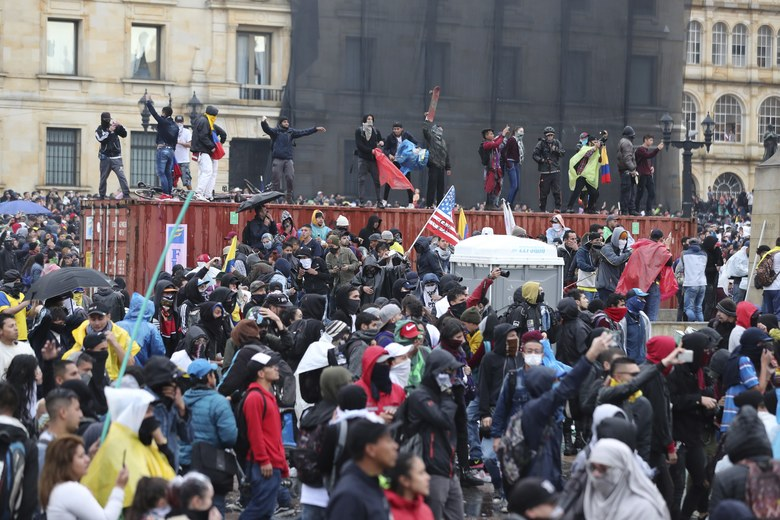 Anti-government protesters shout at the police during a nationwide strike, at Bolivar square in downtown Bogota, Colombia, Thursday, Nov. 21, 2019. Colombia's main union groups and student activists called for a strike to protest the economic policies of Colombian President Ivan Duque government and a long list of grievances. (AP Photo/Fernando Vergara)