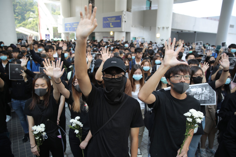 Protesters hold up their hands to represent their five demands during a makeshift memorial for Chow Tsz-Lok at the University of Science and Technology in Hong Kong on Friday, Nov. 8, 2019. Chow, a student from the University who fell off a parking garage after police fired tear gas during clashes with anti-government protesters died Friday, in a rare fatality after five months of unrest that intensified anger in the semi-autonomous Chinese territory. (AP Photo/Kin Cheung)