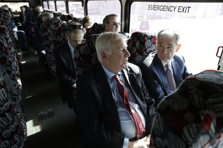 Federal Reserve Bank of Boston President Eric Rosengren, center front, and Federal Reserve Board Chair Jerome Powell, right, participate in a bus tour of East Hartford, Conn., Monday, Nov. 25, 2019. Powell and Rosengren toured a working-class neighborhood in East Hartford and met with residents to get a closer look at their challenges. (AP Photo/Steven Senne)